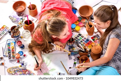Authentic artist children girl paints with set palette watercolor paints palette and brush in morning sunlight. Painting in studio on floor. Older sister teaches younger to draw still lifes.