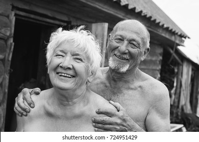 Authentic black and white portrait of funny ridiculous old couple of bearded bold man and charming woman with grey hair and lovely smile. Two grannies are laughing outdoor of bathhouse. Village life.