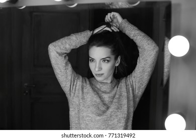 Authentic black & white portrait reflected young mixed raced woman looking at mirror. Brunette lady doing her hairstyle, preparing to photo,dressed casually, having serious mysterious face expression
