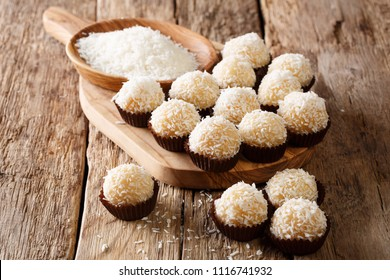Authentic brazilian sweets beijinhos with condensed milk and coconut close-up on the table. horizontal