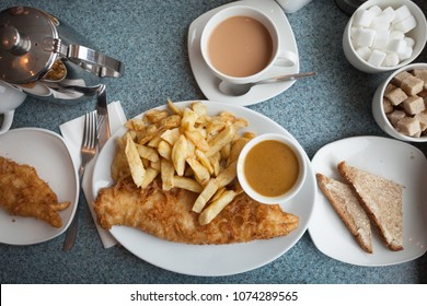 Authentic British fish and chips, with curry sauce, buttered bread and a cup of tea
