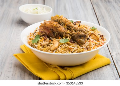 Authentic Chicken Biryani served in a bowl or plate over colourful or wooden background. It's a delicious recipe of Basmati rice mixed with spicy marinated chicken served with salad. Selective focus