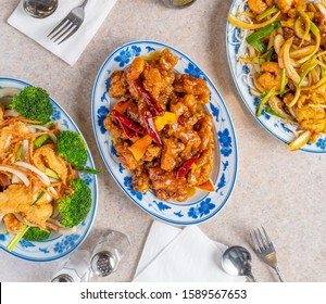 Authentic Chinese American food. Spicy General Tso's chicken, salt and pepper shrimp, and stir fried noodles and vegetables. Spicy and fried Chinese food.