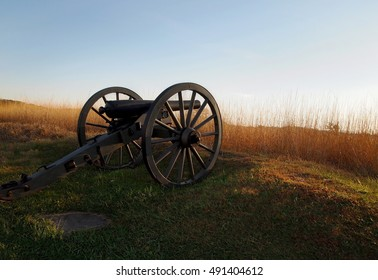 An authentic Civil War cannon sits at the edge of an old battlefield in Gettysburg, Pennsylvania on an autumn evening at sunset.