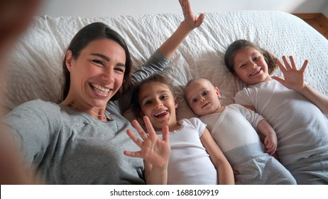 Authentic close up of happy mother with her kids are making a selfie or video call to father or relatives in a bed. Concept of technology, new generation,family, connection, parenthood, authenticity