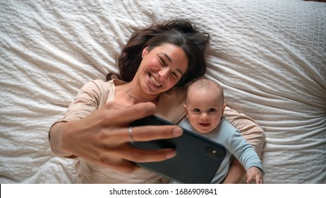 Authentic close up of neo mother and her newborn baby making a selfie or video call to father or relatives in a bed. Concept of technology, new generation,family, connection, parenthood, authenticity