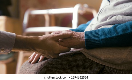 Authentic close up shot of an young man is holding hands of disabled senior woman in wheelchair as sign of care and support. Concept of family, retirement, life,boarding house, help, authenticity