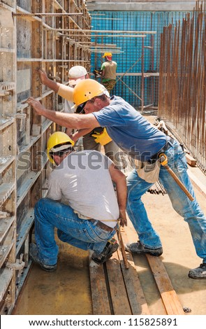 Authentic construction builders working together for positioning concrete formwork frames in place