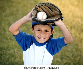 Authentic happy smiling young Latino boy dressed in blue baseball sleeves with cap, glove and ball