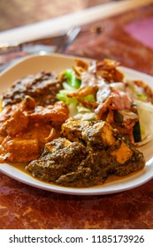 Authentic Indian cuisine buffet plate with tikka masala birista fried onions rajma beans and Saag paneer spinach and cheese