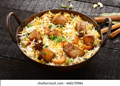 Authentic Indian cuisine-Fish biriyani or pilaf served in a cast iron cooking pot,,Selective focus photograph.