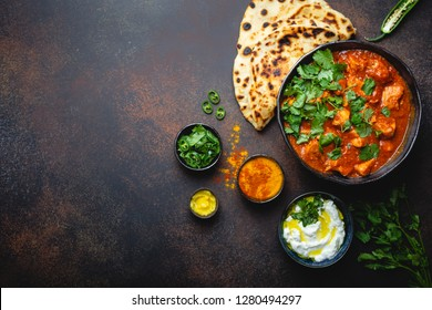Authentic Indian dish Chicken tikka masala with space for text. Spicy curry meat in bowl with fresh bread naan, yoghurt raita sauce on rustic dark background, top view, close up, copy space