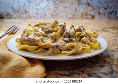 Authentic Italian fettuccine alfredo pasta dish with grilled chicken breast