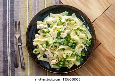 Authentic Italian fettuccine alfredo pasta dish with grilled chicken breast and broccoli