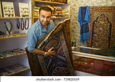 An authentic Kashmiri man and his Kashmiri carpet and art shop, in the main market area of the small town of Leh, Ladakh district, Jammu and Kashmir state, India. Shot in September 2017.