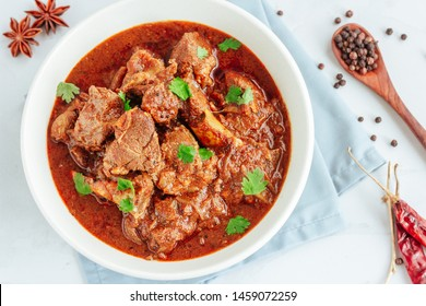 Authentic Lamb Vindaloo Traditional Fiery Red Goan Curry of Lamb. Lamb Curry / Lamb Vindaloo in a Bowl on White Background with Scattered Raw Spices