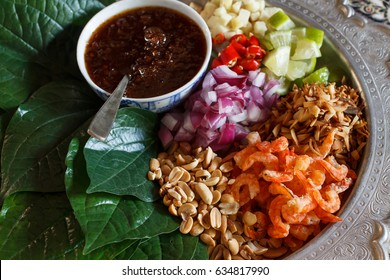 """Authentic local of Thai cuisine. Thai appetizer called """"Miang Kham"""", some of nutritious snack wrapped in leaves with a sweet and salty sauce."""