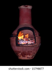 An authentic Mexican chimnea with a lit fire inside isolated on a black background