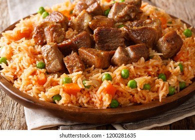 Authentic Mexican rice with green peas and carrots served with spicy pork close-up on a plate on the table. horizontal