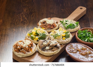 Authentic Mexican sopes with grated cheese and salsa