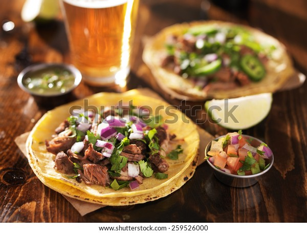 authentic mexican tacos with beer on wooden table shot with selective focus