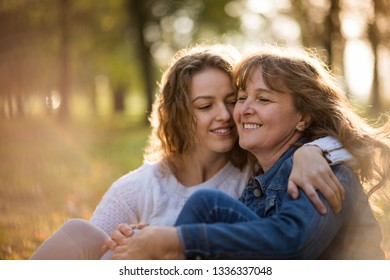 Authentic moment of young woman embracing her mother outdoor in nature