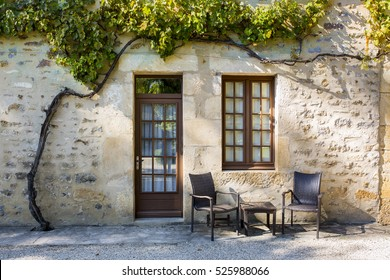 Authentic old house in Burgundy with glass wooden door and window, chairs and table just in front and big grape tree