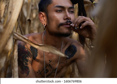 Authentic outdoor shot of gorgeous shirtless male artist with many interesting tattoo on fit tanned body, posing gracefully on corn field, wears dreadlocks and piercing. Fashion and beauty concept.