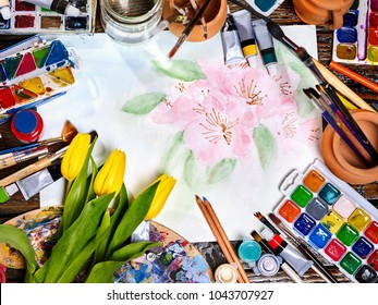 Authentic paint brushes still life in art class school. Group of brush in clay jar. Bouquet of flowers as symbol of spring discounts. Copy space for text. Tulips in foreground.