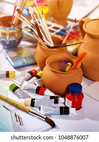 Authentic paint brushes still life on table in art class school as drawing course. Group of brush in clay jar. Discounts on goods for artists.