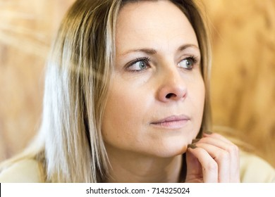 Authentic pensive blonde young adult woman portrait. Close up horizontal crop