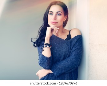 Authentic portrait of a dreamy girl standing outdoors and looking far away, genuine beauty of a woman with natural makeup