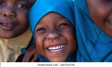 Authentic portrait of happy rural african girls wearing burka are smiling in camera. Concept: charity, poverty,life, happiness, authenticity, religion, children