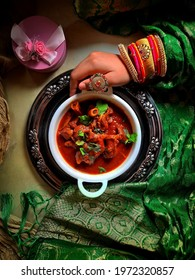 Authentic Rajasthani Jungli Maas Recipe close-up in the bowl on the table with an indian woman hand , top view. focus