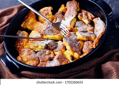 Authentic recipe of austrian torn pancake kaiserschmarrn with raisins and icing sugar on top, cutlery on a black baking dish on a dark concrete table, close-up