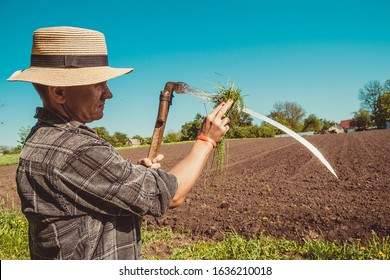 Authentic rural farmer in straw hat clean scythe with grass. Agriculture worker. Sharp blade. Vegetable garden. Farm implements. Rustic background. Work countryside. Brutal country man. Manual labor