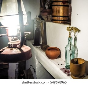 Authentic rustic interior: inside the village hut. Wooden and pottery ware, antique lamp, vases, dried flowers, whitewashed walls.