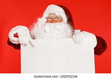 Authentic Santa Claus with blank banner on red background. Space for design