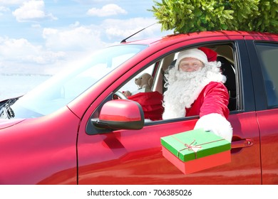 Authentic Santa Claus holding gift box while sitting in car with Christmas tree on it's top