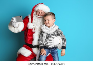 Authentic Santa Claus taking selfie with little boy on color background