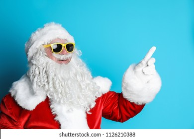 bc2cce03cce88 Authentic Santa Claus wearing sunglasses on color background