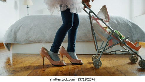 Authentic shot close up of little girl is playing with stroller toy and doll wearing her mother high heeled shoes in parents bedroom..