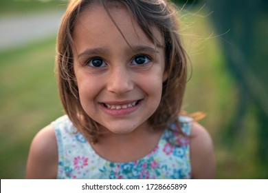 Authentic shot of happy carefree little girl is smiling in camera on a green nature background in a sunny day.
