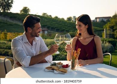 Authentische Aufnahme von glücklichen Paar in Liebe ist es, romantisches Abendessen zusammen zu genießen und mit weißen Gläsern zu jubeln, um ihren Jahrestag und zeitlose Liebe auf malerischem Weinhintergrund zu feiern.