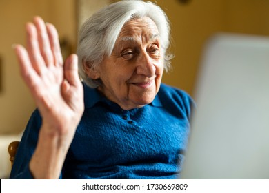 Authentic shot of a happy grandmother is making a video call to relatives with a laptop at home. Concept of technology, modern generation,family, connection, authenticity