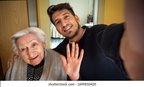 Authentic shot of happy grandson and grandmother in a wheelchair are having fun to take a selfie or make a video call to relatives at home. Concept of technology,family, connection, authenticity