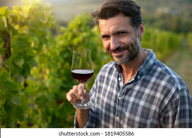 Authentic shot of happy successful male winemaker is tasting a flavor and checking red wine quality poured in transparent glass on vineyards background at sunset.