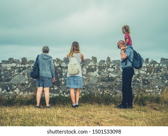 Authentic shot of real family by the coast in the fog. Young mother, toddler and grandparents.