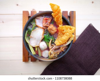 Authentic Thai-style noodle soup with fishballs, squids, crispy wonton and special homemade red sauce