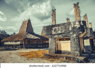 Authentic tomb, straw roof house. Sumba village. Indonesia. The ethnic settlement on the cloudy sky background. The striking feature is that traditional huts intermingle with tombs. Indonesia.